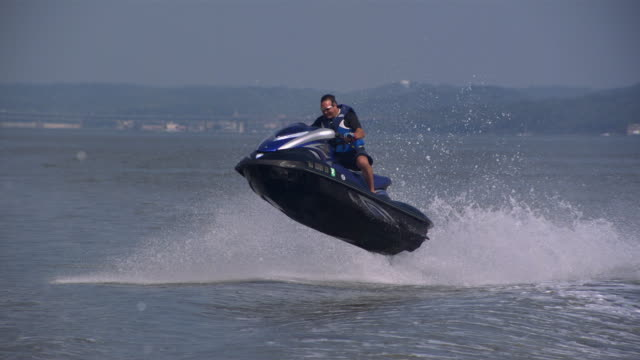 ws ts zo slo mo shot of man wearing sunglasses standing up on jet ski while jumping several waves / new york, united states - acquascooter video stock e b–roll