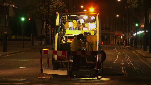 ms t/l shot of man with van working on road repairs at night / london, united kingdom  - van stock videos & royalty-free footage