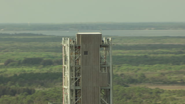 cu aerial zo shot of man working at top of rocket stand with surrounding landscape / florida, united states  - kennedy space center stock-videos und b-roll-filmmaterial