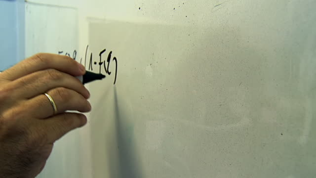 CU Shot of Man writes equation on whiteboard / London, United Kingdom