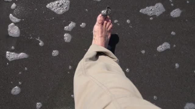 MS POV Shot of mans feet walking along dark sandy ocean beach / Crescent City, California, United States