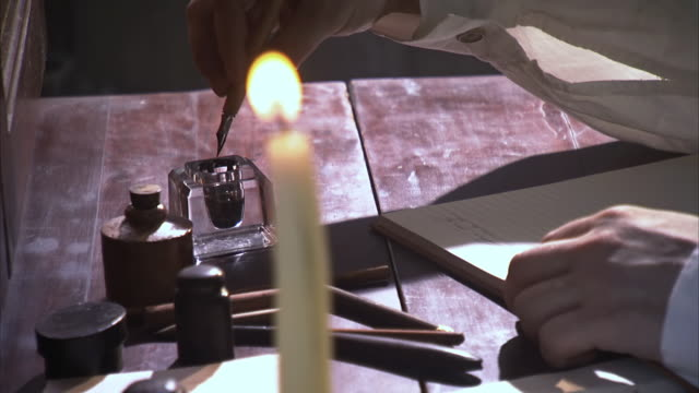 vidéos et rushes de cu pa ts shot of mans hand as he dips his fountain pen in ink and writes in his diary by candlelight / middleburg, virginia, united states - plume