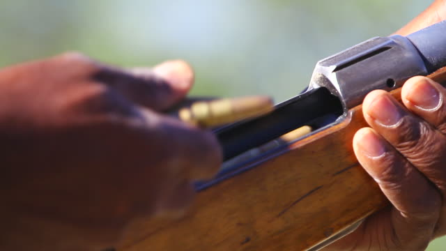 vidéos et rushes de cu shot of man's hands loading high caliber hunting rifle / ongava, kunene, namibia - fusil