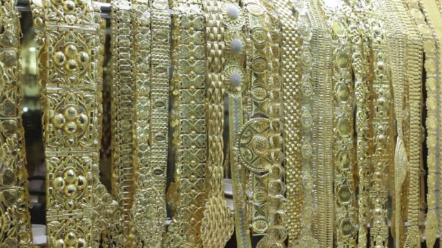CU TD Shot of many gold necklaces in store / Dubai,  United Arab Emirates