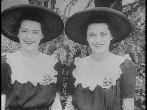 Shot of many pairs of twins posing for camera / Louise and Lois Bailey identical twin sisters smile at each other in matching dresses and hats /...