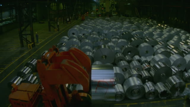 MS AERIAL Shot of Many steel rolls in warehouse with trucks