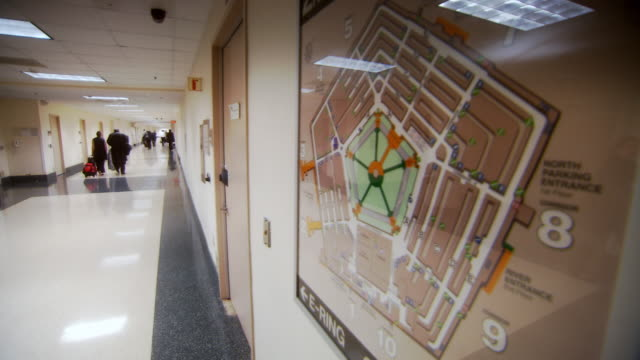 ms shot of map of pentagon building on wall and people walking down hallway / arlington, virginia, united states - pentagono arlington virginia video stock e b–roll