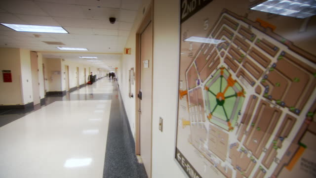 MS PAN Shot of map of pentagon building on wall and people walking down hallway / Arlington, Virginia, United States