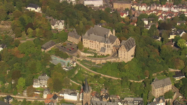 stockvideo's en b-roll-footage met ms aerial shot of marburg castle surrounded by trees / germany - kerktoren