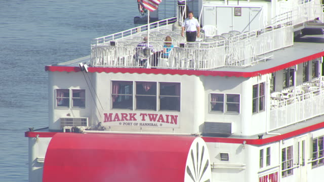 cu aerial ts shot of mark twain port of hannibal sign above paddle wheel housing on mark twain riverboat traveling south on mississippi river / hannibal, missouri, united states - mark twain stock videos & royalty-free footage