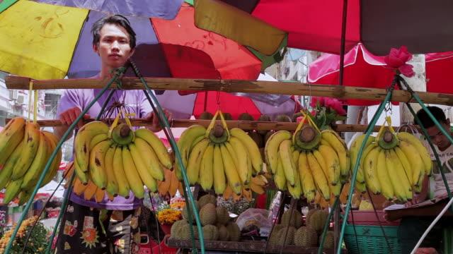 stockvideo's en b-roll-footage met ms shot of market vendor in front of bananas at market / yangon, yangon division, myanmar  - zonwering