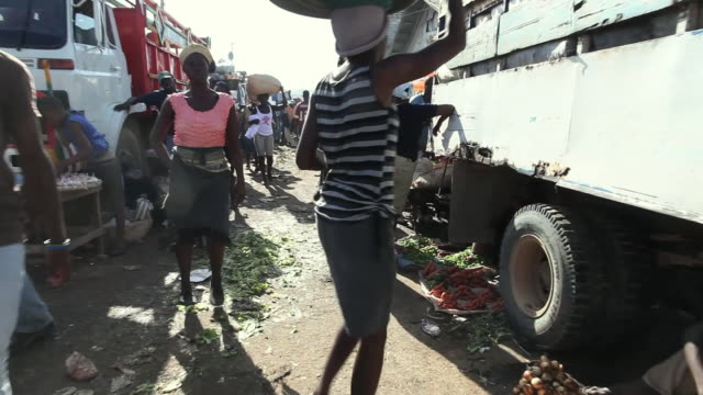 ms pov shot of market vendors sell fruits and vegetables and people walk around and shop / port-au-prince, haiti - ポルトープランス点の映像素材/bロール