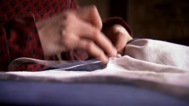 cu pan r/f shot of mary pickersgills hands as she sews a star on the star spangled banner / baltimore, maryland, united states  - cucire video stock e b–roll