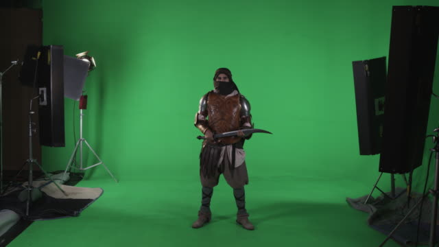 stockvideo's en b-roll-footage met shot of masked man in arabic armor making intimidating motion with sword. against green screen. - zwaard