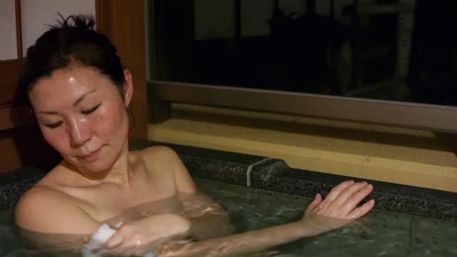 vídeos y material grabado en eventos de stock de cu shot of mature asian woman in japanese hot bath at night - una sola mujer madura
