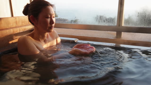 CU Shot of Mature Asian Woman in Japanese hot bath in morning