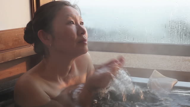 cu shot of mature asian woman in japanese hot bath in the morning - 50 seconds or greater stock videos & royalty-free footage