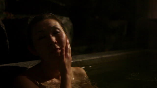 cu shot of mature asian woman in japanese outdoor hot bath at night - one mature woman only stock videos and b-roll footage