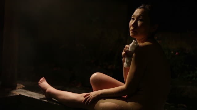 MS Shot of Mature Asian Woman in Japanese outdoor sitting near hot bath at night