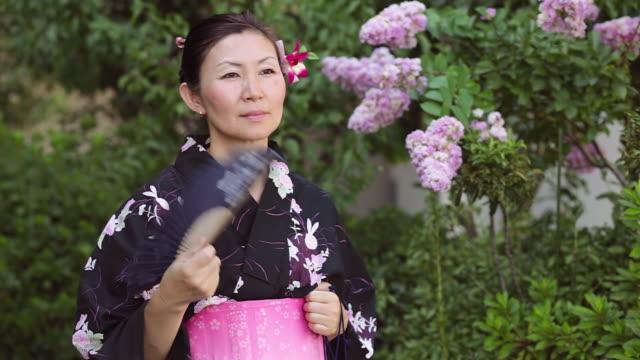 cu shot of mature woman in traditional japanese clothing and smiling calling yukata with fan / tokyo, japan - yukata video stock e b–roll