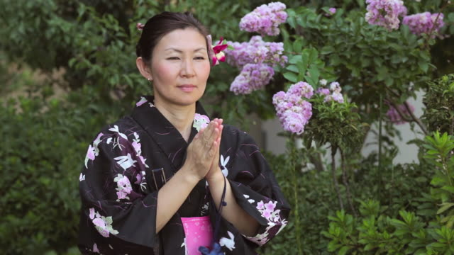 cu shot of mature woman in traditional japanese clothing calling prays / tokyo, japan - yukata video stock e b–roll
