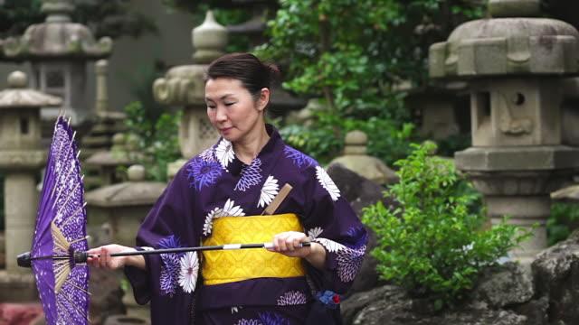 ms shot of mature woman in traditional japanese clothing calling yukata with fan and umbrella / tokyo, japan - yukata video stock e b–roll
