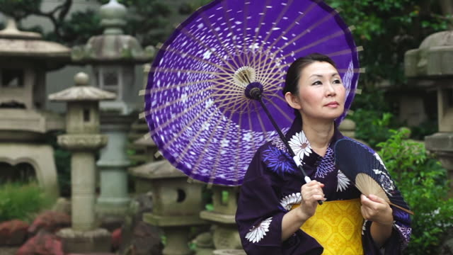 CU PAN Shot of Mature woman in traditional Japanese clothing calling Yukata with fan and umbrella / Tokyo, Japan