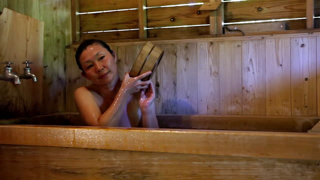 ms shot of mature woman soaks in a traditional japanese hot bath called onsen / yufuin, oita, japan - solo una donna matura video stock e b–roll