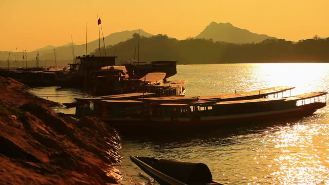 ms shot of mekong river bank in sunset light with wooden boats dock / luang prabang, laos - travelling light stock videos & royalty-free footage