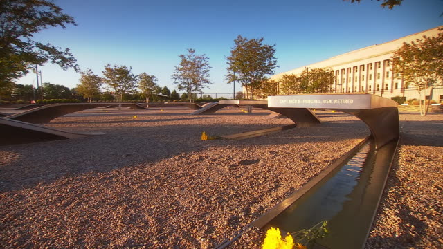 MS TD Shot of memorial captain jack punches with yellow flowers under metal bench with water running under at September 11th memorial outside pentagon building / Arlington, Virginia, United States