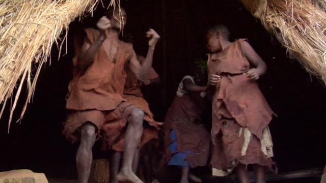 MS Shot of men and woman of batwa doing tribe dance on native song AUDIO / kigez, kabale, uganda