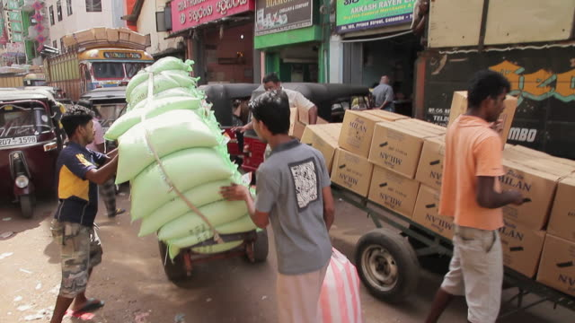 ms pov shot of men carrying heavy loads and passing delivery trailer at pettah market / colombo, western province, sri lanka - sri lanka people stock videos & royalty-free footage