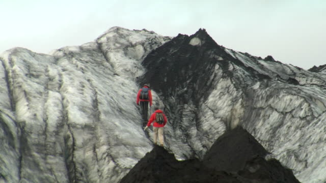 ms shot of men climbing up mountain side / vestmannaeyjar, sudhurland, iceland - wiese stock videos & royalty-free footage