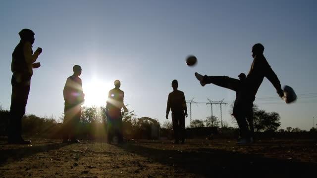 MS LA SLO MO Shot of Men kicking ball to each other / Johannesburg, Gauteng, South Africa