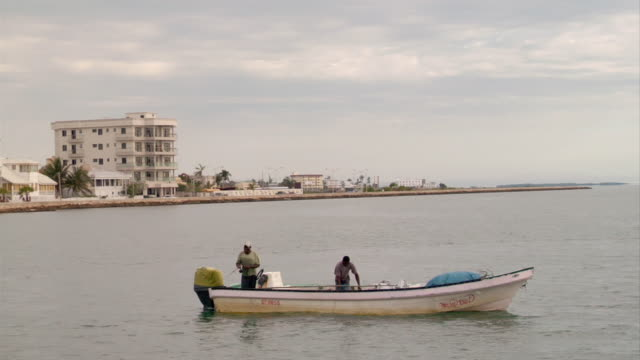 ms shot of men on small boat fishing in water / abergris caye, belize, belize - wiese stock videos & royalty-free footage