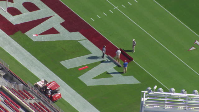 MS AERIAL Shot of men painting red color on football field at University of Alabama Bryant Denny Stadium football stadium / Tuscaloosa, Alabama, United States