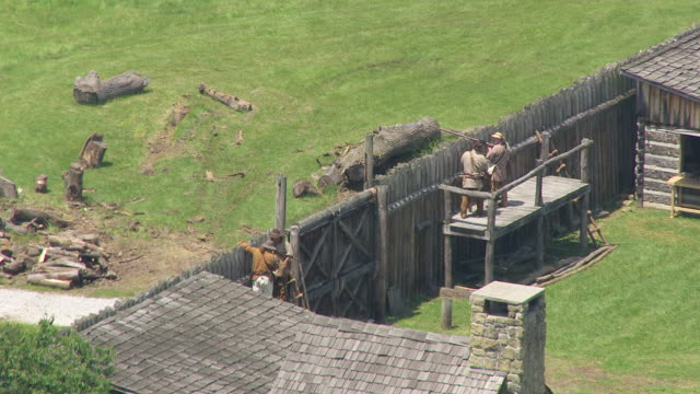 MS AERIAL Shot of men standing at fence with rifles during Fort Randolph Reenactment / Point Pleasant, West Virginia, United States
