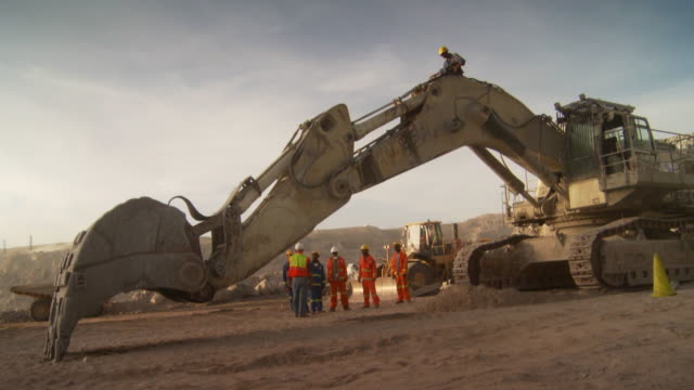 MS Shot of men standing behind arm of excavator / Namibia
