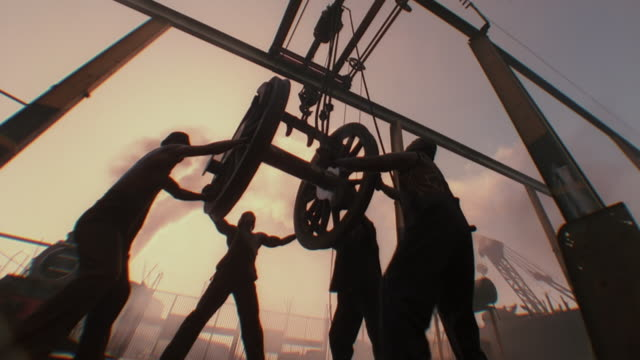 MS LA Shot of men steadying heavy wheel on crane above railway track / South Africa