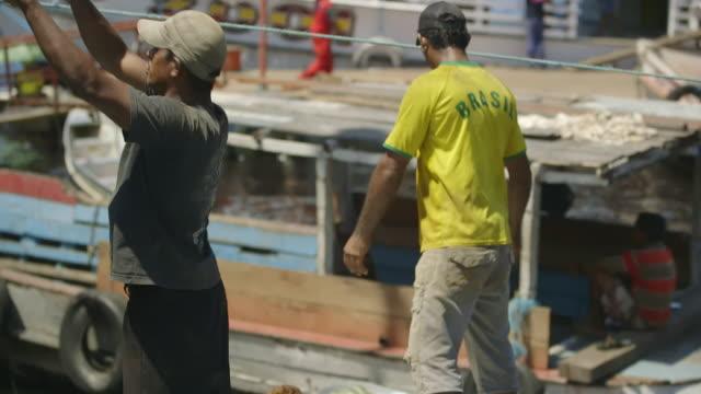 ms tu td shot of men unloading squash from boat using assembly line system / iquitos, maynas, peru - baseballmütze stock-videos und b-roll-filmmaterial