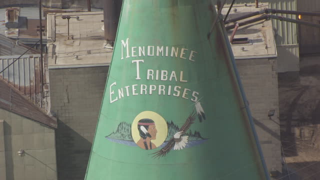 CU AERIAL Shot of Menominee Tribal Enterprises sign on green tee pee building at Menominee Sawmill / Wisconsin, United States