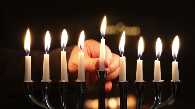 CU Shot of menorah eighth gets lit by shamash candle and placing in middle for eight / Los Angeles, California, United States