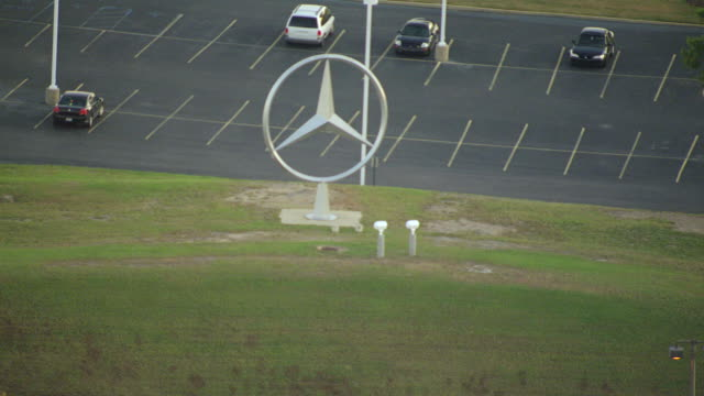 ms aerial shot of mercedes symbol by parking lo at mercedes benz us international auto factory in tuscaloosa county / alabama, united states - mercedes benz stock videos and b-roll footage