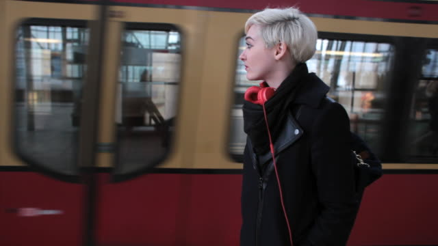 vídeos de stock e filmes b-roll de ms shot of metro train taking off with woman watching at train station then walking/ berlin, germany  - cabelo curto comprimento de cabelo