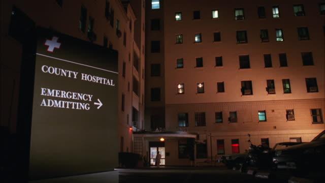 vídeos de stock e filmes b-roll de ws shot of metropolitan hospital with sign of 'county hospital emergency entrance' - hospital