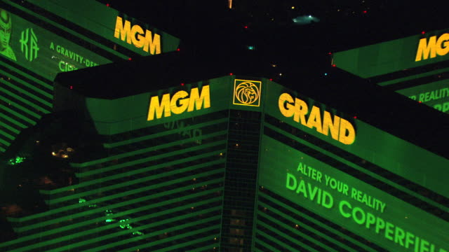 ms aerial shot of mgm grand hotel exterior neon signs at night / las vegas, nevada, united states - mgm grand las vegas stock videos & royalty-free footage