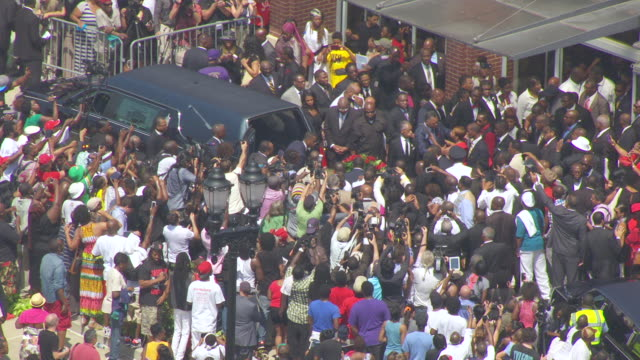 MS AERIAL Shot of Michael Browns casket is loaded into hearse and Al Sharpton and Jesse Jackson hug family and friends outside Friendly Temple Missionary Baptist Church / St Louis, Missouri, United States