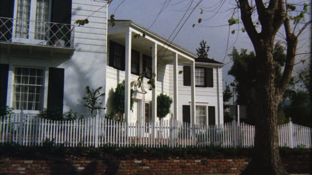 ms shot of middle class two story white colonial house - picket fence stock videos and b-roll footage