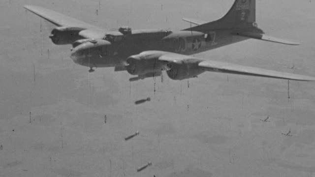 stockvideo's en b-roll-footage met ms aerial ts shot of military airplanes in flight and bombs dropping on city - bom