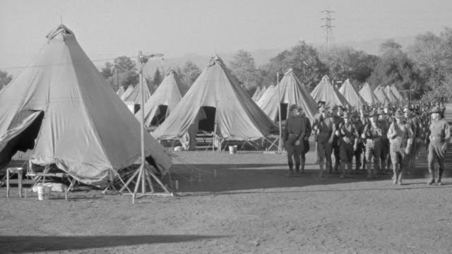 WS Shot of Military camp as soldiers march near their tents